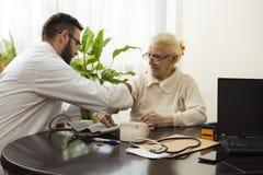 一个私有医生` s办公室 老年医学专家医生采取患者并且测量她的血压 免版税图库摄影