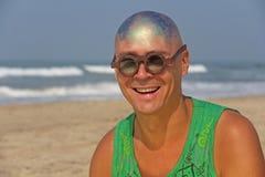 一个秃头和异常的年轻人,一位畸形人,戴一副发光的秃头和圆的木眼镜在海滩和海的背景 免版税图库摄影