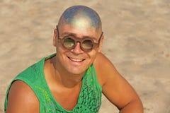 一个秃头和异常的年轻人,一位畸形人,戴一副发光的秃头和圆的木眼镜在海滩和海的背景 图库摄影