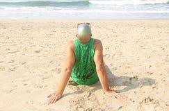 一个秃头和异常的年轻人,一位畸形人,戴一副发光的秃头和圆的木眼镜在海滩和海的背景 免版税库存照片