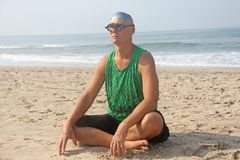 一个秃头和异常的年轻人,一位畸形人,戴一副发光的秃头和圆的木眼镜在海滩和海的背景 库存照片