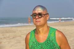 一个秃头和异常的年轻人,一位畸形人,戴一副发光的秃头和圆的木眼镜在海滩和海的背景 库存图片