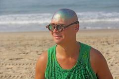 一个秃头和异常的年轻人,一位畸形人,戴一副发光的秃头和圆的木眼镜在海滩和海的背景 免版税库存图片
