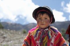一个秘鲁男孩的画象在五颜六色的手工制造成套装备穿戴了 免版税库存照片