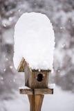 一个积雪的鸟房子在冬天 免版税库存图片