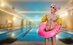 一个稀薄,滑稽的人赤裸与圆环在水池附近 库存图片
