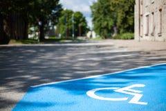 一个空的有残障的后备的停车位的特写镜头在城市绘了与一个白色轮椅标志的蓝色在黑沥青 免版税库存照片