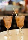一个空的杯子在一个透明杯子的被冰的焦糖热奶咖啡咖啡在木背景 葡萄酒口气过程 图库摄影