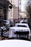 一个空的都市咖啡馆大阳台的春天照片与白色桌布和chakered毯子的在椅子 免版税库存照片