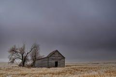 一个空的领域的老被放弃的谷仓 免版税图库摄影