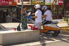 一个穿着体面的迷人的夫人站立谈话与有一辆摩托车的两三个人在明媚的阳光 库存图片