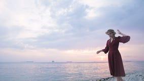 一个穿着红色夏装、戴着草帽的漂亮小女孩,在海岸岩石上谨慎地皱起眉头 股票录像