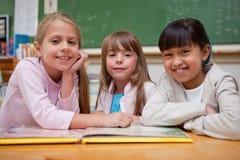 读一个童话的微笑的女小学生对他们的同学 免版税库存照片