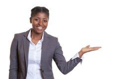 一个笑的非洲女商人的介绍 免版税图库摄影