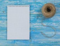 一个笔记本和一条概略的绳索在一张蓝色木桌上 库存照片