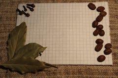 一个笔记本用咖啡豆、月桂树叶子和丁香笔记的 免版税库存图片