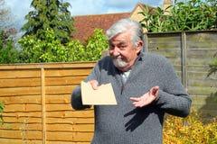 给一个简单的棕色信封的老人 库存照片