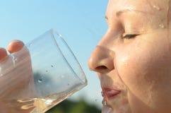 一个简单的欧洲少妇是从一个玻璃烧杯的饮用水反对蓝天 图库摄影