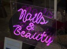 一个简单的蓝色霓虹广告标志说钉子和秀丽在入口对修指甲客厅 图库摄影