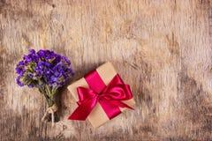 一个箱子以在老破旧的木背景的惊奇 有缎丝带的礼物盒 背景和纹理 免版税库存照片