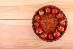 一个篮子用形成一个圈子里面在一张木桌上的新鲜的红色草莓 与叶子的健康莓果在轻的背景 库存照片