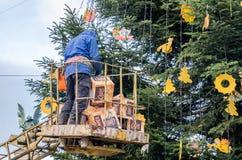 一个篮子的工人在机器轻拍的高度装饰玩具和装饰圣诞树在自由大街前面o的 免版税库存图片