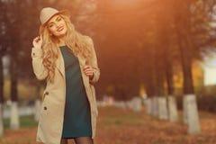 一个米黄帽子的年轻美丽的女孩和外套在公园秋天停放 有红色嘴唇的时兴的女性 Copyspace 库存图片