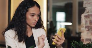 一个紧张的女商人在咖啡馆使用一个智能手机,写坐的消息 技术互联网手机画象 影视素材
