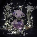 一个紫色熊女孩的玩偶有珍珠装饰品的 免版税库存图片