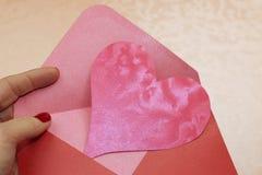 一个红字信封和桃红色心脏 免版税库存照片