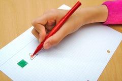 画一个红色三角和一个绿色正方形的孩子 免版税库存照片