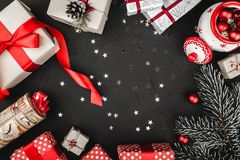 一个红色丝带、圣诞节礼物、树玩具、闪耀的星和常青分支的上部顶视图在石黑背景 图库摄影