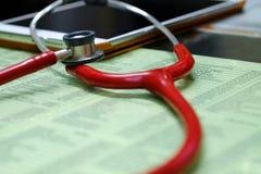 一个红色听诊器和一种片剂在doctor& x27; s书桌 库存照片