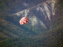 一个红色和白色降伞的飞将军下降反对森林山背景  库存图片
