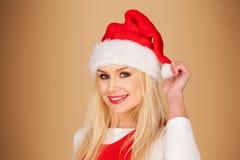 一个红色圣诞老人帽子的快活的少妇 库存图片