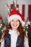一个红色圣诞老人帽子的激动的女孩 库存照片