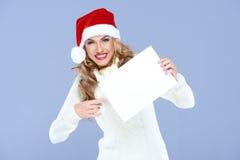 一个红色圣诞老人帽子的活泼的妇女 免版税库存照片