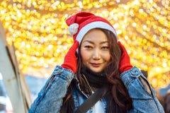 一个红色圣诞老人项目帽子的一个美丽的亚裔女孩在光附近站立和圣诞节诗歌选和微笑 免版税库存照片