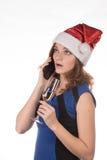 一个红色圣诞节帽子的年轻美丽的女孩有一杯的可汗 图库摄影