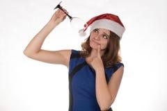 一个红色圣诞节帽子的年轻美丽的女孩有一杯的可汗 库存照片