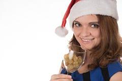 一个红色圣诞节帽子的年轻美丽的女孩有cha的一块玻璃的 库存照片