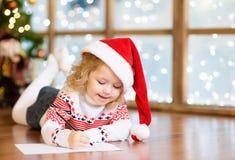 一个红色圣诞节帽子的愉快的女孩写信的给圣诞老人Clau 免版税库存图片