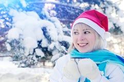 一个红色圣诞节帽子的美丽的微笑的白肤金发的女孩 库存照片