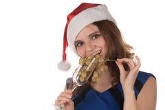 一个红色圣诞节帽子的美丽的性感的女孩拿着一块玻璃  免版税库存图片