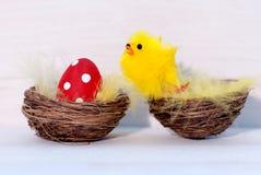 一个红色复活节彩蛋和黄色小鸡在巢 免版税库存照片