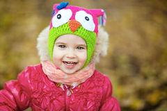 一个红色夹克和帽子的微笑的小女孩有猫头鹰的 图库摄影