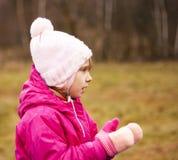 一个红色夹克和白色帽子的一个孩子在街道上使用,拍他的在手套的手 秋天 图库摄影