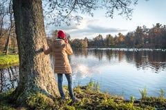 一个红色帽子佩带的耳机的一个女孩享受aut的看法 库存图片