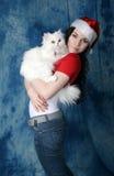 一个红色帽子和一件夹克的一个女孩有一只白色蓬松猫的 图库摄影