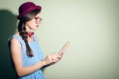 一个红色帽子和玻璃的典雅的俏丽的女孩读书的 免版税库存图片